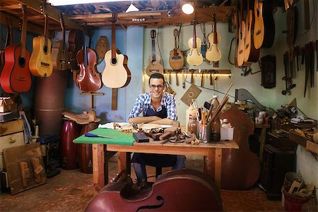 diego_cervo (artist) - Lute maker shop and acoustic music instruments: portrait of a young adult artisan sitting at his desk and smiling at camera. He is surrounded by many guitars, mandolins and violins. Stock Photo - Budget Royalty-Free & Subscription, Code: 400-08507324