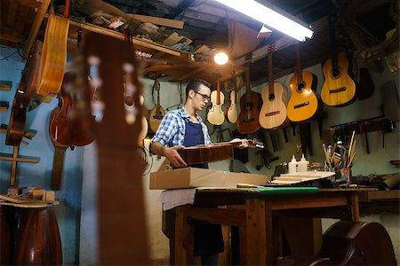 diego_cervo (artist) - Lute maker shop and acoustic music instruments: a young adult artisan fixes an old classic guitar, then stores it in a cardboard case for his client. Wide shot Stock Photo - Budget Royalty-Free & Subscription, Code: 400-08507322
