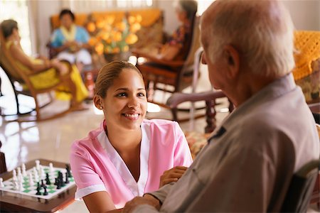 diego_cervo (artist) - Old people in geriatric hospice: young attractive hispanic woman working as nurse takes care of a senior man on wheelchair. She talks with him then goes away to help other patients Stock Photo - Budget Royalty-Free & Subscription, Code: 400-08507323