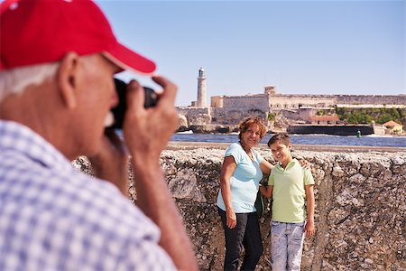 diego_cervo (artist) - Happy tourists on holidays. Hispanic people traveling in Havana, Cuba. Grandfather, grandmother and grandchild during summer travel, with senior man taking photos with camera Stock Photo - Budget Royalty-Free & Subscription, Code: 400-08706432