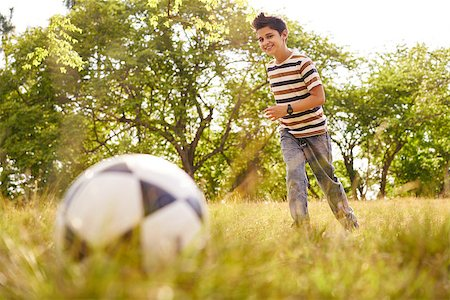 Adolescence and leisure activity. Young kid playing soccer in park, running towards the ball, smiling happy. Stock Photo - Budget Royalty-Free & Subscription, Code: 400-08706440
