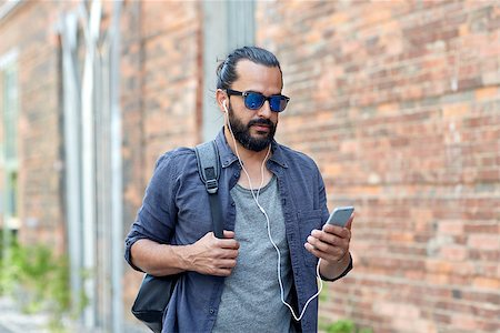 people, technology, travel and tourism - man with earphones, smartphone and bag walking along city street and listening to music Stock Photo - Budget Royalty-Free & Subscription, Code: 400-08758079