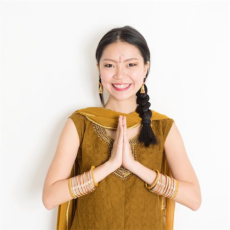 punjabi - Portrait of young mixed race Indian Chinese girl in traditional punjabi dress with greeting pose, standing on plain white background. Stock Photo - Budget Royalty-Free & Subscription, Code: 400-08785745