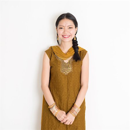 punjabi - Portrait of young mixed race Indian Chinese woman in traditional Punjabi dress smiling, standing on plain white background. Stock Photo - Budget Royalty-Free & Subscription, Code: 400-08785742