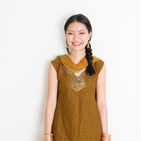 punjabi - Portrait of young mixed race Indian Chinese female in traditional Punjabi dress smiling, standing on plain white background. Stock Photo - Budget Royalty-Free & Subscription, Code: 400-08785743