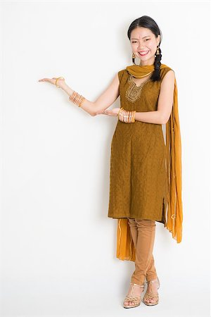 punjabi - Portrait of young mixed race Indian Chinese woman in traditional punjabi dress hands showing somethings, full length standing on plain white background. Stock Photo - Budget Royalty-Free & Subscription, Code: 400-08787339