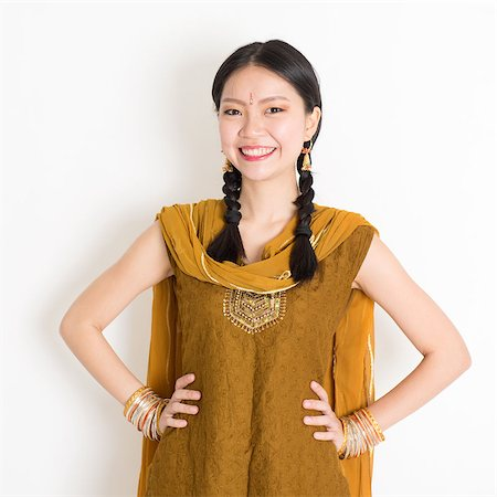 punjabi - Portrait of beautiful mixed race Indian Chinese woman in traditional Punjabi dress smiling, standing on plain white background. Stock Photo - Budget Royalty-Free & Subscription, Code: 400-08787344