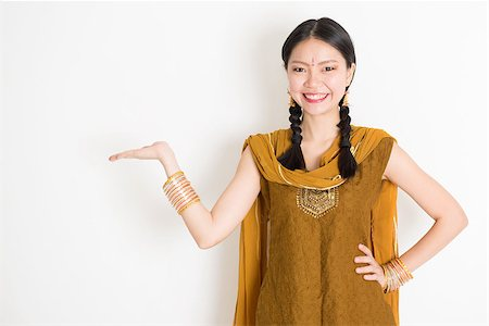 punjabi - Portrait of young mixed race Indian Chinese female in traditional punjabi dress hand holding somethings, standing on plain white background. Stock Photo - Budget Royalty-Free & Subscription, Code: 400-08787345