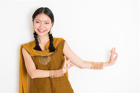 punjabi - Portrait of young mixed race Indian Chinese girl dancer in traditional punjabi dress with dancing pose, standing on plain white background. Stock Photo - Budget Royalty-Free & Subscription, Code: 400-08787346
