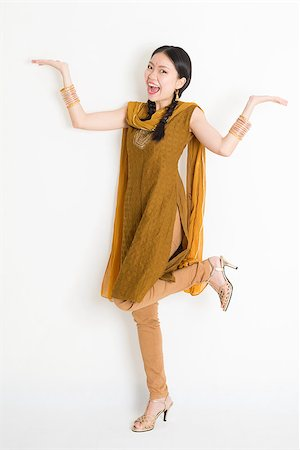 punjabi - Portrait of excited mixed race Indian Chinese woman in traditional punjabi dress palms showing something, full length standing on plain white background. Stock Photo - Budget Royalty-Free & Subscription, Code: 400-08787348
