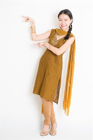 punjabi - Portrait of young mixed race Indian Chinese woman in traditional punjabi dress fingers pointing at copy space, full length standing on plain white background. Stock Photo - Budget Royalty-Free & Subscription, Code: 400-08787340