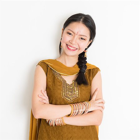 punjabi - Portrait of arms crossed mixed race Indian Chinese woman in traditional Punjabi dress smiling, standing on plain white background. Stock Photo - Budget Royalty-Free & Subscription, Code: 400-08787341