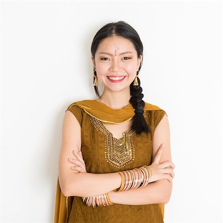 punjabi - Portrait of arms crossed mixed race Indian Chinese female in traditional Punjabi dress smiling, standing on plain white background. Stock Photo - Budget Royalty-Free & Subscription, Code: 400-08787342
