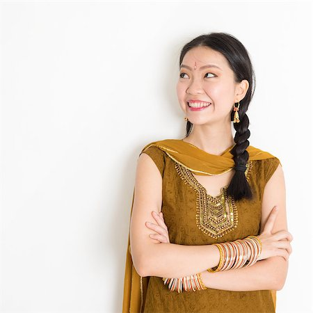 punjabi - Portrait of arms crossed mixed race Indian Chinese woman in traditional Punjabi dress looking side upward, standing on plain white background. Stock Photo - Budget Royalty-Free & Subscription, Code: 400-08787343