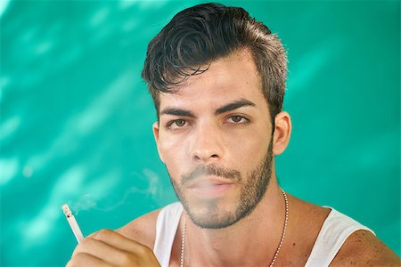 diego_cervo (artist) - Real Cuban people and emotions, portrait of young hispanic man from Havana, Cuba looking at camera with serious expression, smoking cigarette and blowing smoke Stock Photo - Budget Royalty-Free & Subscription, Code: 400-08816311