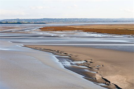 Sea coast at low tide. The tides can vary greatly, at roughly 14m between high and low water marks. One of France's most recognizable landmarks. View from the top of the mount Saint Michael's, France Stock Photo - Budget Royalty-Free & Subscription, Code: 400-08831586