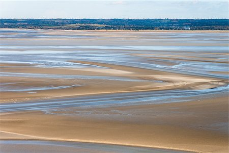 Sea coast at low tide. The tides can vary greatly, at roughly 14m between high and low water marks. One of France's most recognizable landmarks. View from the top of the mount Saint Michael's, France Stock Photo - Budget Royalty-Free & Subscription, Code: 400-08831587