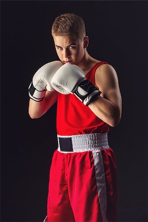 Young handsome boxer sportsman in red boxer suit and white gloves standing on black backgound. Copy space. Stock Photo - Budget Royalty-Free & Subscription, Code: 400-08861358