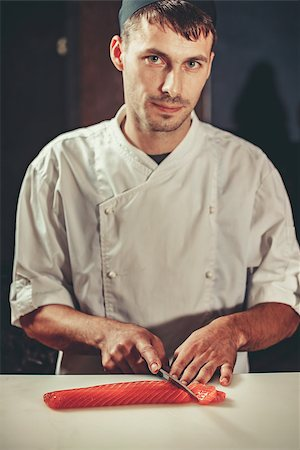 Young chef coock dressed in white uniform cut salmon fish on the table in restaurant. He is working on sashimi. Preparing traditional japanese sushi set in interior of modern professional kitchen Stock Photo - Budget Royalty-Free & Subscription, Code: 400-08890818