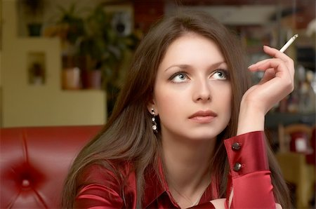 Sexy green eyed brunette in red with smoking cigarette Stock Photo - Budget Royalty-Free & Subscription, Code: 400-03914236