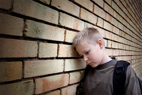 upset boy leaning against a wall Stock Photo - Royalty-Free, Artist: mikdam, Image code: 400-03914944