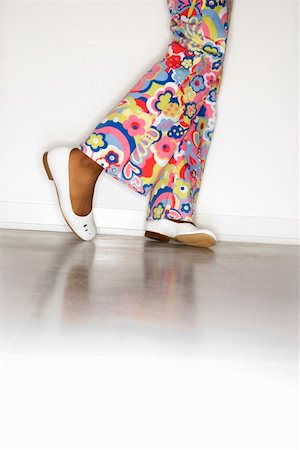 preteen girl feet - Close-up of African-American teen girl's legs with floral pants and white shoes against white background. Stock Photo - Budget Royalty-Free & Subscription, Code: 400-03921343