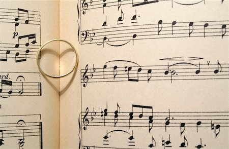 Golden wedding ring on old sheet music, casting a heart shaped shadow Stock Photo - Budget Royalty-Free & Subscription, Code: 400-03933668