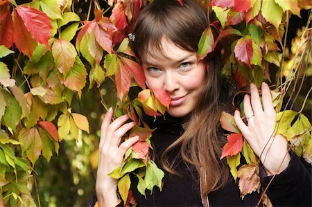 pile leaves playing - beautiful girl makes eyes surrounded with autumn leaves Stock Photo - Budget Royalty-Free & Subscription, Code: 400-03956720