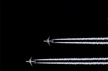 Two jet aircraft flying in a horizontal and parallel formation with smoke trails, set against a black sky background. Stock Photo - Budget Royalty-Free & Subscription, Code: 400-03950942