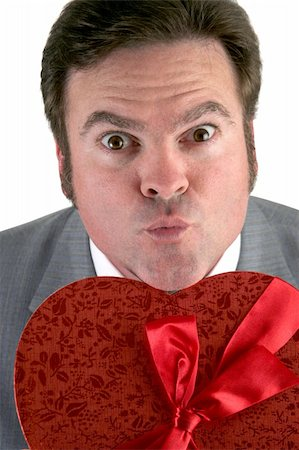 A closeup photo of a man holding a box of valentine candy and puckering up for his valentines day kiss. Stock Photo - Budget Royalty-Free & Subscription, Code: 400-03967422