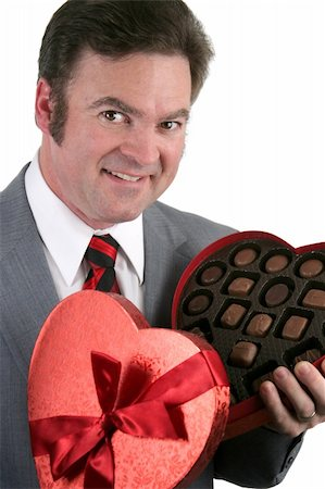 Closeup portrait of a handsome, well-dressed man holding a box of valentines candy.  White background. Stock Photo - Budget Royalty-Free & Subscription, Code: 400-03967460