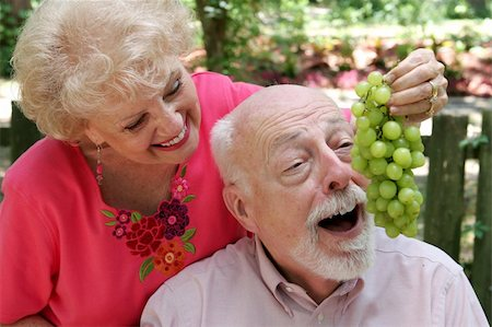 A senior couple joking around.  She is feeding him grapes. Stock Photo - Budget Royalty-Free & Subscription, Code: 400-03969323
