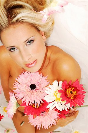 Beautyful young naked woman lying on the white tissue, holding bunch of flowers in the hand Stock Photo - Budget Royalty-Free & Subscription, Code: 400-03974503