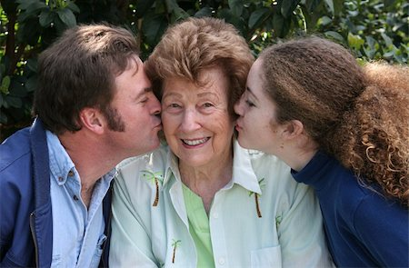 A pretty grandmother receiving kisses from her family and smiling. Stock Photo - Budget Royalty-Free & Subscription, Code: 400-03970484