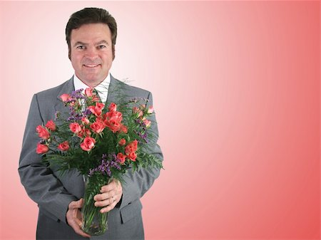 dozen roses - A handsome husband in a suit holding a bouquet of pink sweetheart roses over a pink packground. Stock Photo - Budget Royalty-Free & Subscription, Code: 400-03972317