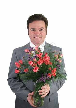 dozen roses - A handsome husband in a suit holding a bouquet of pink sweetheart roses over a pink packground. Stock Photo - Budget Royalty-Free & Subscription, Code: 400-03972318
