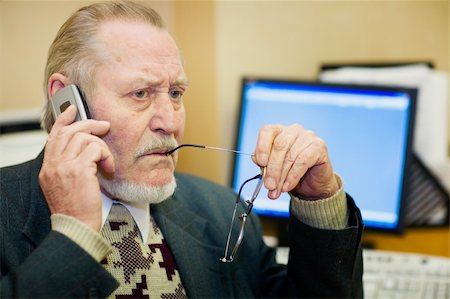 Mature businessman talking on the phone, checking out a document on his computer monitor. Stock Photo - Budget Royalty-Free & Subscription, Code: 400-03989090