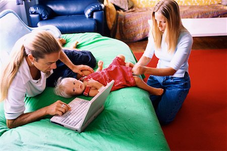 Father using laptop and mother changing diaper Stock Photo - Premium Royalty-Free, Code: 604-00229856