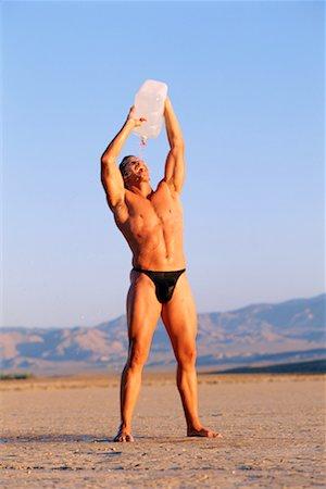 Man in desert drinking water Stock Photo - Premium Royalty-Free, Code: 604-00231592