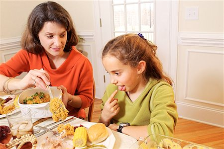 Daughter making gagging gesture to food during meal/ Stock Photo - Premium Royalty-Free, Code: 604-00233719