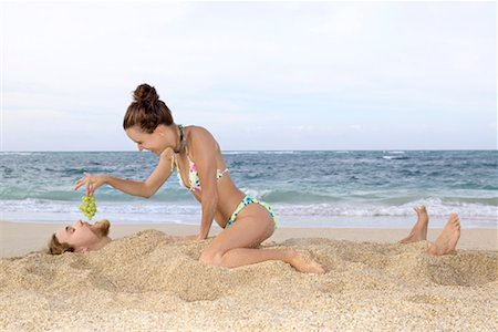 Woman feeding grapes to man buried in sand/ Stock Photo - Premium Royalty-Free, Code: 604-00278417