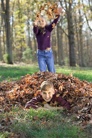 pile leaves playing - Children playing in leaves/ Stock Photo - Premium Royalty-Free, Code: 604-00365051