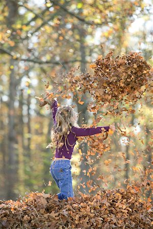 pile leaves playing - Girl playing in leaves/ Stock Photo - Premium Royalty-Free, Code: 604-00365060