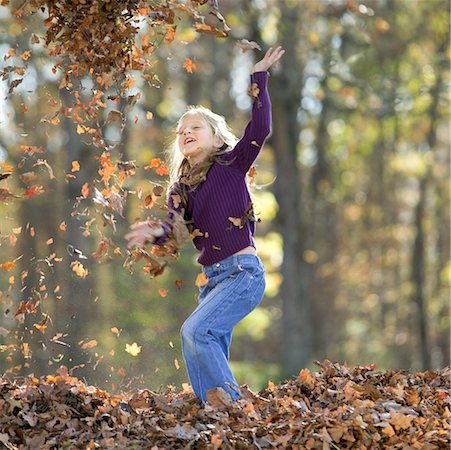 pile leaves playing - Girl playing in leaves/ Stock Photo - Premium Royalty-Free, Code: 604-00365061