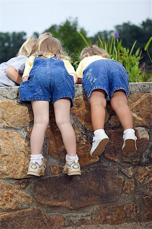 Girls looking over wall Stock Photo - Premium Royalty-Free, Code: 604-00757379