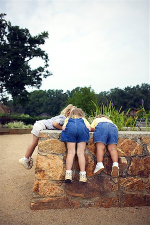 Girls looking over wall Stock Photo - Premium Royalty-Free, Code: 604-00757380