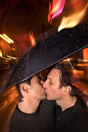 Homosexual couple kissing under an umbrella Stock Photo - Premium Royalty-Free, Code: 604-00758471