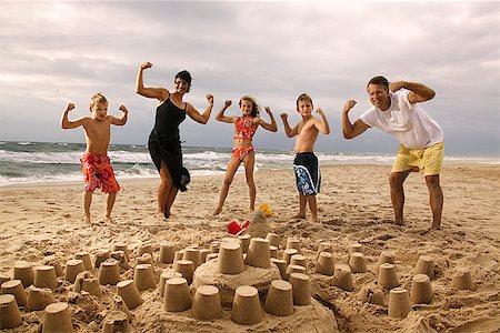 Family flexing on beach Stock Photo - Premium Royalty-Free, Code: 604-00761436