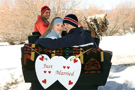 Couple in horse drawn sleigh with just married sign Stock Photo - Premium Royalty-Free, Code: 604-00762175