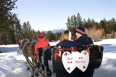 Couple in horse drawn sleigh with just married sign Stock Photo - Premium Royalty-Free, Code: 604-00762173